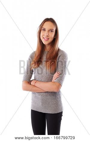 Mid portrait of pretty slim young girl keeping arms crossed over white isolated background. Wearing grey sweater and black trousers. Folded hands, wear warm knitted sweater, isolated over white