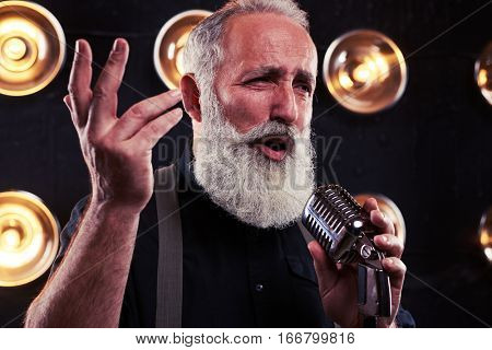 Side view of seductive handsome man with long beard in shirt raised one hand up isolated over spotlights. Exhilarated young male singer