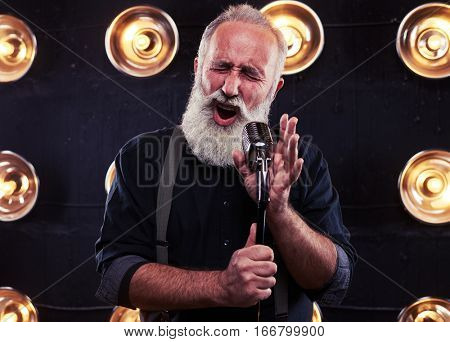 Close-up of impassioned man singing in a silver vintage microphone wearing dark shirt and suspenders. Using studio microphone and posing at the camera