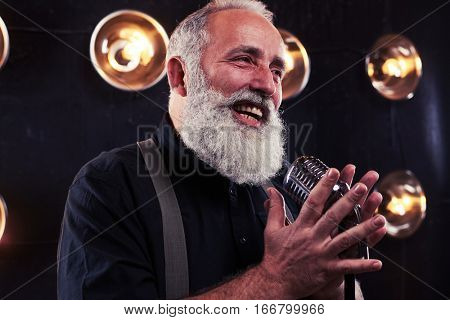 Close-up of emotional man in white shirt and suspenders holding a retro silver studio microphone over the background of blurred spotlights.