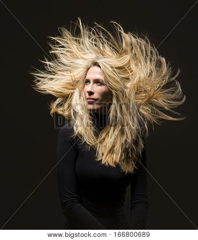 Blonde woman with extreme hair, black dress and background