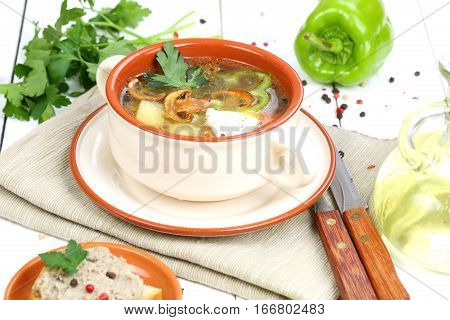 Mushroom soup from field mushrooms with a potato and greens in a ceramic cup