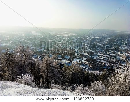 landscape with mountain city is flooded with sunlight in winter