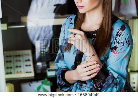 beautiful female model showing jewelry on her hands . In the background showcase with jewelry.Small accessories for fashionistas