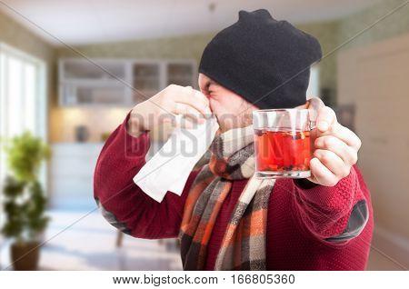 Young Man With Tea Mug Blowing Nose