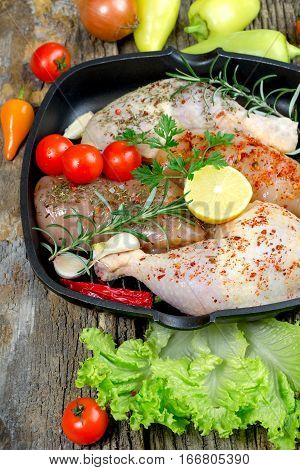 Raw chicken drumstick and raw chicken breast with spices