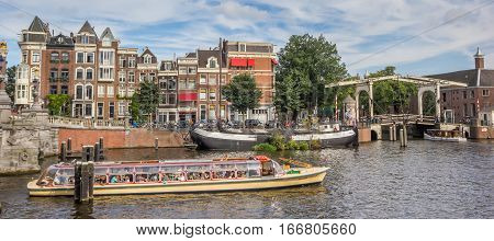 AMSTERDAM, NETHERLANDS - SEPTEMBER 18, 2016: Tourists taking a river cruise in Amsterdam, Holland