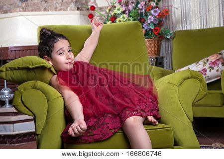 Cute lovlely tired middle eastern girl with dark red dress and collected hair waking up stretching arms on the green uncomfortable sofa at home interior. studio shot.