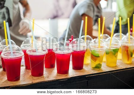 Various Soft Drinks In Plastic Cups With A Straws On Display At A Street Market. Selective Focus