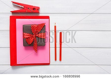 Valentines day scrapbook, wedding or other holiday decorations background. Tools for creating cards, pencils for cut and paste, colored paper and present box on white wood. Above view, flat lay