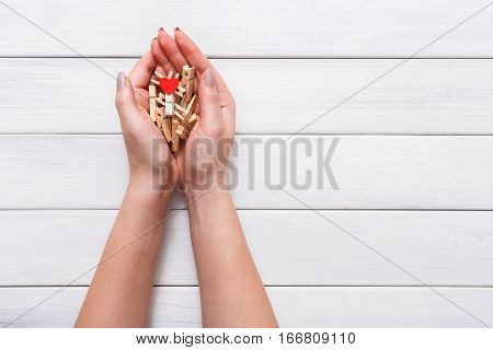 Valentine background with clothespins and red heart in woman's hands at rustic white wood planks. Happy lovers day card mockup, copy space