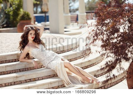 Fashionable Sexy Elegant Lady In Fashion Dress Lying On Steps. Beautiful Young Brunette Woman With C