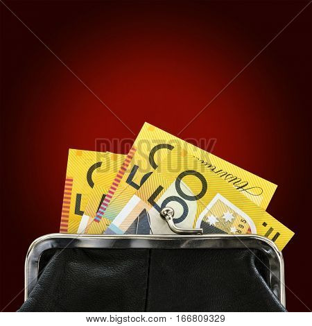 Australian money in purse over glowing red background.