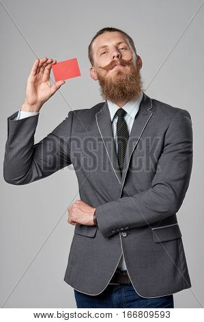 Very proud hipster business man with beard and mustashes in suit showing credit card over grey background