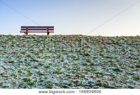 Wooden bench on top of a frosty dike. It is a sunny day in the Dutch winter season and the grass is covered with hoarfrost.