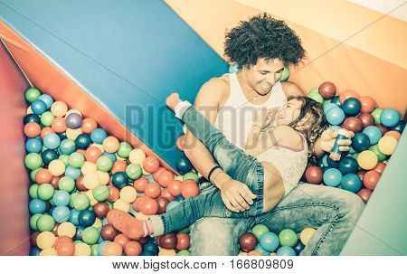 Latin american dad playing with mixed race daughter on ball pit swimming pool at kindergarten playroom - Family concept with happy multiracial child and father having fun at kid toyroom - Retro filter