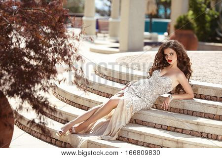 Fashionable Sexy Woman In Luxury Dress. Beautiful Young Brunette With Curly Hair Lying On Steps. Ele