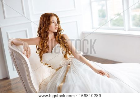 Bride in beautiful dress sitting on sofa indoors in white studio interior like at home. Trendy wedding style shot in full length. Young attractive caucasian red hair model like a bride against big window tender resting.