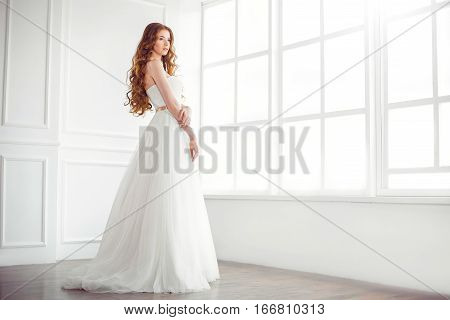 Wedding. Beautiful bride indoors at big window in full lenght looking away. Side view