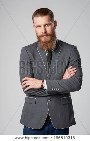 Confident stylish business man with beard and mustashes in suit standing with folded hands looking to the side over grey background