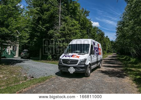 Pocono Lake, Pennsylvania, July 11, 2016: A FedEx van is parked by a house where the employee is making a delivery.
