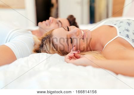 Sensual foreplay by cute couple in bedroom