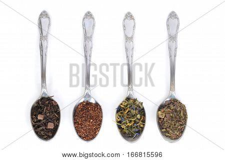 assorted organic tea on spoons on white