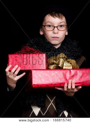 small boy or cute nerd kid in glasses hat and fashionable knitted scarf on black background holds red present boxes with golden bow