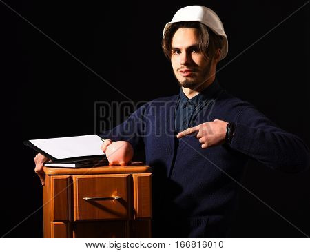 handsome bearded builder or foreman in blue sweater and helmet on serious face holding wooden bedside with tablet and pink piggy bank on black studio background