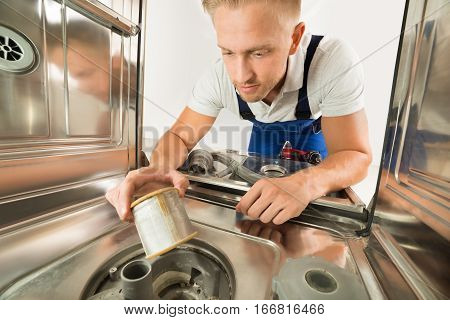 Young Man In Overall Repairing Dishwasher In Kitchen