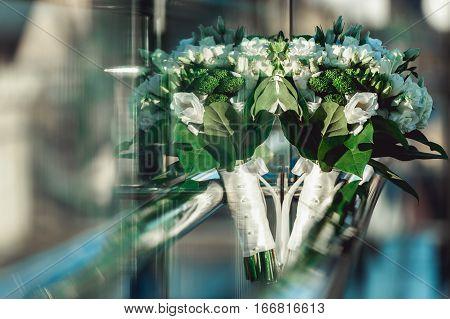 wedding bouquet on the chrome handrail on the glass balcony