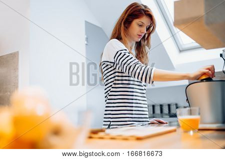 Beautiful woman squeezing oranges in order to prepare hommade juice