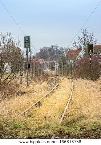 Overgrown rails in front of a village
