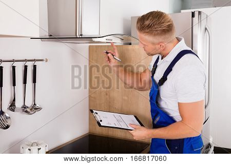 Young Male Repairman With Clipboard Checking Kitchen Extractor Filter
