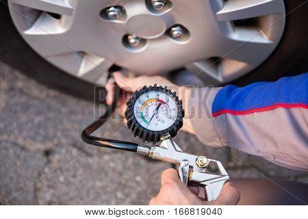 Person Measuring Car Tyre Pressure With Pressure Gauge