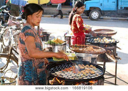 Pyin U Lwin Myanmar - 18 January 2010: Woman cooking traditional Burmese street food in Pyin U Lwin