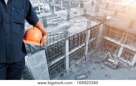engineer holding orange helmet on office buildings construction background.