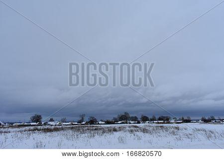the dark and gloomy sky on the horizon winter village