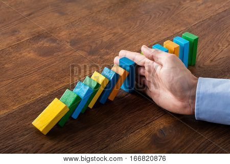Person Hand Stopping Falling Dominoes From Continuous Toppled On Wooden Desk. Business Risk Concept