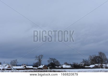 somber sky with dark clouds and very snowy valley