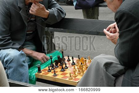 Two men play chess on a bench in the park.