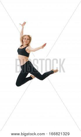 Slim pretty blonde in black top and leggings gracefully jumping in studio