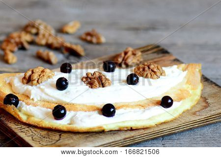 Fried stuffed omelette recipe. Omelette with soft cheese, walnuts and black currants on a wooden board. Simple and yummy dish using egg. Closeup