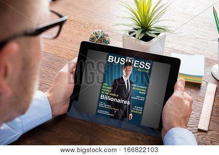 Close-up Of A Businessman Reading Online Magazine On Digital Tablet At Wooden Desk