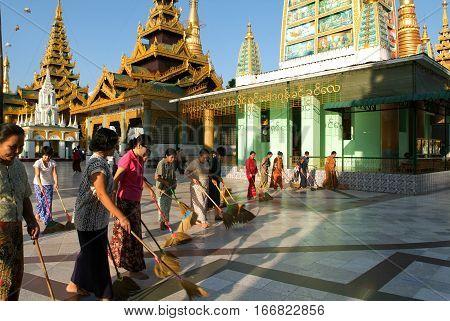 Yangon Myanmar - 9 January 2010: People cleaning with brooms the area of the Shwedagon Pagoda in Yangon on Myanmar