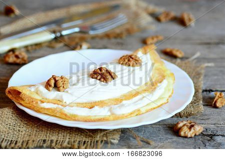 Stuffed omelette on the plate. Homemade fried omelette with soft cheese and walnuts. Tasty breakfast recipe with eggs. Cutlery, shelled walnuts on a wooden table. Vintage style. Closeup