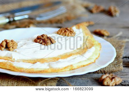 Egg omelette with sweet filling on the plate. Hearty omelette with soft cheese and walnuts. Fork, knife, raw shelled walnuts on a wooden background. Closeup