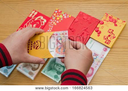 ZhongshanChina-Jan 262017:man preparing a red pocket for Chinese new year.January 28 is the 1st day of year Rooster & sending receiving red pockets is a traditional culture in China.