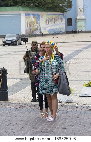 Kiev Ukraine - August 24 2916: Girls in national costumes are photographed on a background of a soldier of the National Guard
