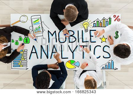 High Angle View Of Businesspeople Drawing The Mobile Analytic On Office Desk In Office